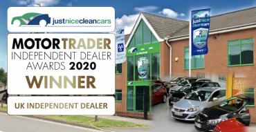Used car dealership with cars for sale and Motor Trader UK Independent Dealer Winner Award 2020 logo outside garage building