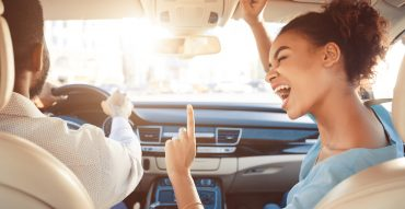 Happy couple singing along to music playing while driving in a car