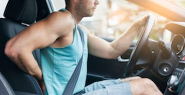Driver with back pain in car seat from driving long journey in teh wrong seat position